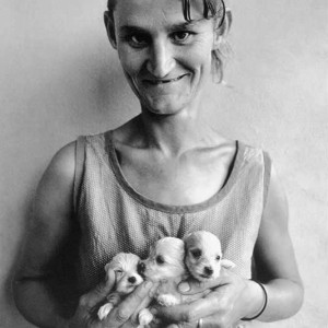Wife of abattoir worker holding three puppies, Orange Free State, 1994